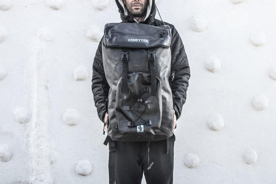 c5949d0b18b0 Man holding a waterproof backpack.